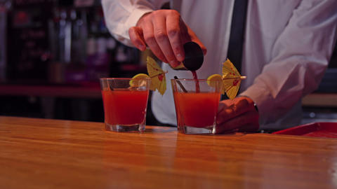 Bartender pouring cocktail into glass at bar counter in bar Live Action