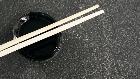 Chopsticks and soy sauce on black stone slate Live Action