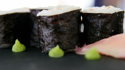 Maki Sushi served on grey stone slate with soy sauce Live Action
