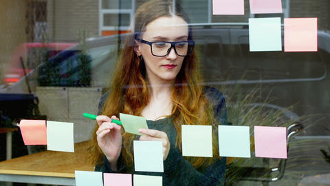 Business executive reading at sticky note while having cup of coffee Live Action