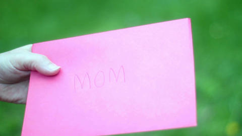 Daughter handing mom a mothers day card in pink loving... Stock Video Footage
