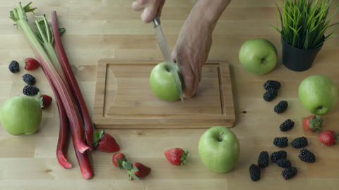 Man is cutting the apple into pieces on the kitchen table view from above Footage