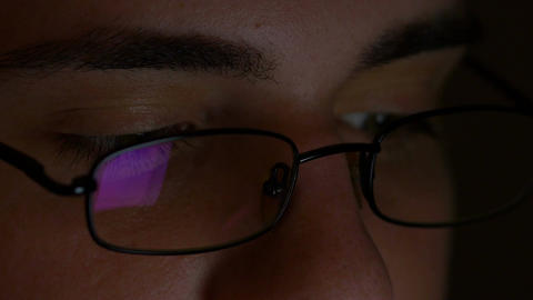 Closeup of teenager eyes wearing glasses and browsing internet on tablet pc in a Footage