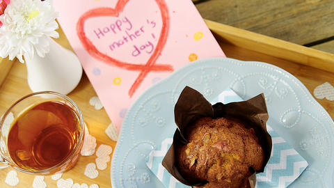 Cupcake, tea, flower vase and happy mothers day greetings card in tray Live Action