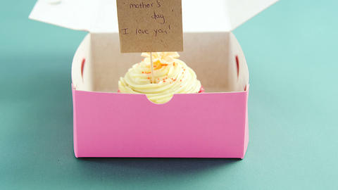 Cupcake with happy mother day card against green background Live Action