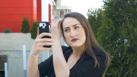 Beautiful woman checking her makeup and hair using camera of smartphone before t Footage