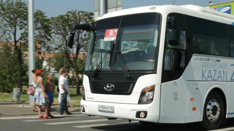 Bus with Kazan Universiade Logo on Side Drives along Street Footage