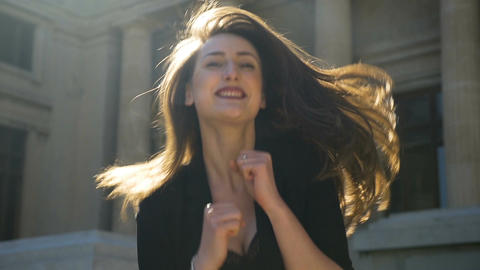 Young happy girl dancing and bouncing and jumping full of joy in the city in slo Footage