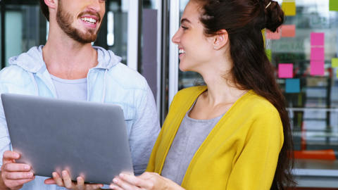 Male and female executives having discussion over laptop, Live Action
