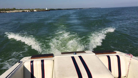 Back of speedboat sailing off into lake erie waters with lighthouse tower in bac Footage