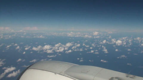 Aerial of clouds over the sea with blue sky from inside an airplane Footage