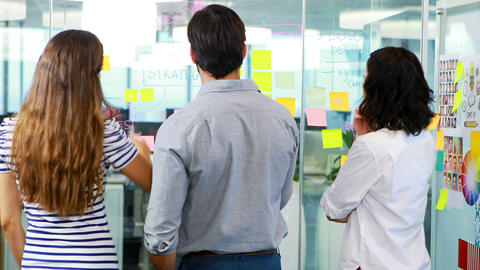 Group of executives discussing over sticky notes Live Action