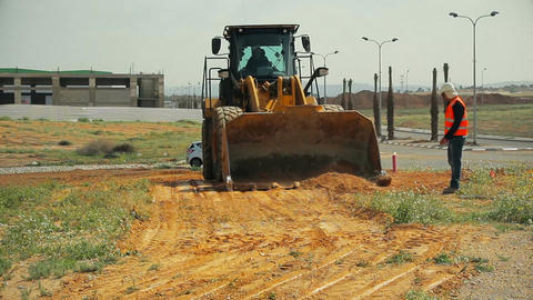Tractor with a bulldozer moving soil at a construction site. Construction contra Filmmaterial