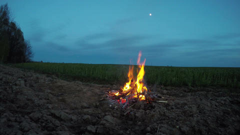 Bonfire burning outdoors by the field, 4K Footage