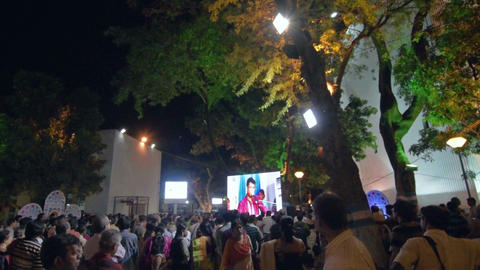 A male singer performing and seen in big screen amongst audience