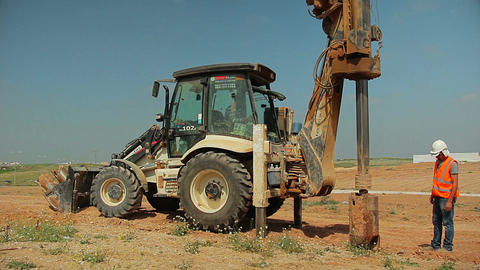 Tractor with a drilling device at a construction site. Contractor supervising hi Filmmaterial
