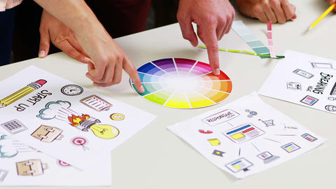 Graphic designers discussing over color swatch at desk Footage