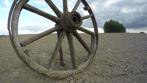 Rustic weathered wooden horse carriage wheel in the field, time lapse 4K Footage