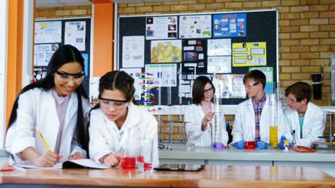 School girls writing in journal book while experimenting in laboratory at school Footage