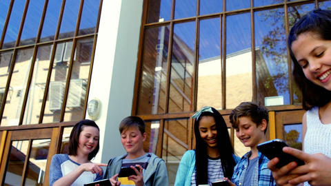 Group of school friends using mobile phone outside school Footage