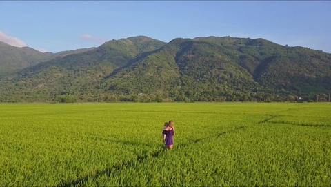 Aerial Backside View Woman Carries Girl in Arms among Fields Footage