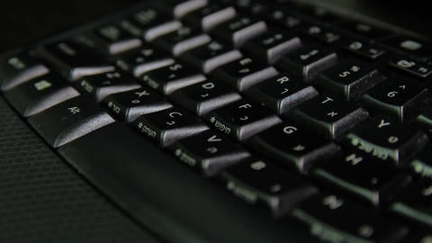 Man typing on a keyboard with letters in Hebrew and English - Wireless keyboard Filmmaterial