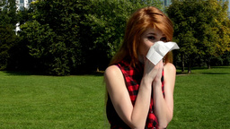 Young attractive woman is in the park - woman blowing her nose with handkerchief Footage