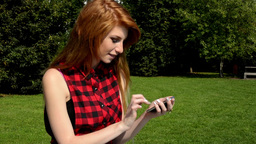 Young attractive woman is in the park - woman works on the smartphone (sms) - na Footage