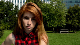 Young attractive woman has a serious expression and looks into the camera - natu Footage