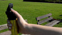 woman in the park - woman holds a pepper spray - grass in the background - natur Footage
