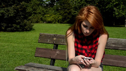 Young attractive woman sits on bech in the park and smiles - woman works on the  Footage