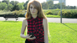 young attractive woman goes in park and listens to music on smartphone - other p Footage