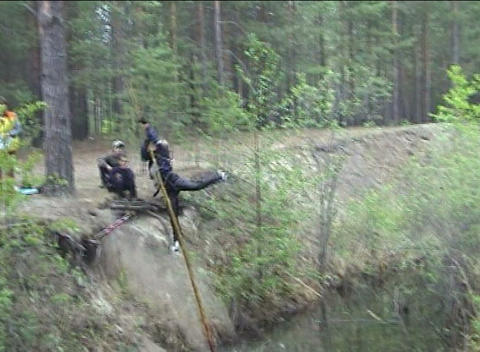 Sportswoman overcomes water ditch with falling Footage