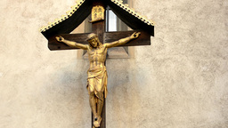 jesus on the cross - crucifix - wall with nature (flowers) and candles Footage