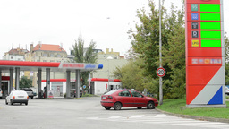 fuel station - passing cars - trees and grass - information panel with fuel pric Footage