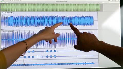 Two people pointing at music waves on the screen Live Action