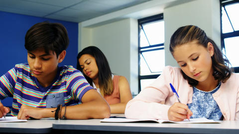 Schoolboy cheating during exam in classroom Live Action