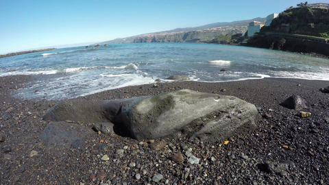 View of black sand beach with rock by the ocean, time lapse 4K Footage