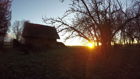 Landscape with old clay barn and sun rising over rural fields, time lapse 4K Footage