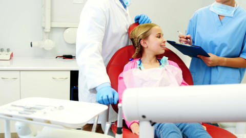 Dentist interacting with female dental assistant Live Action