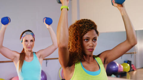 Determined women performing aerobics with dumbbells Live Action