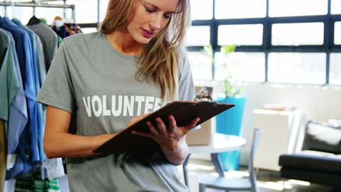 Happy female volunteer writing on clipboard Footage