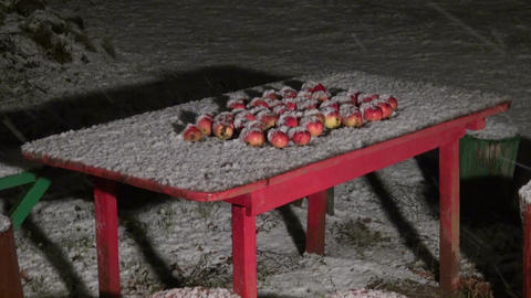 Apples on table in the winter with falling snow Footage
