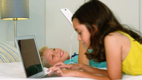 Siblings sitting back to back and using digital tablet, laptop in bedroom Live Action