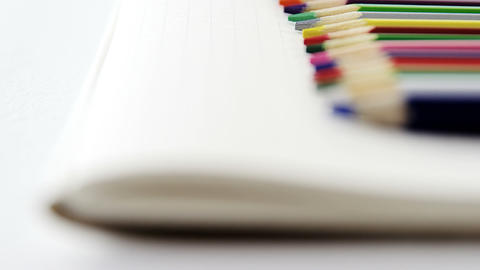 Colored pencils kept on the book Live Action