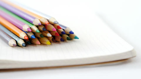 Colored pencils kept on the book Live-Action