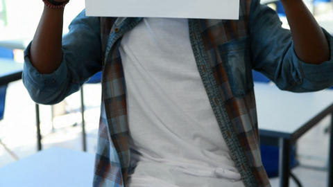 Schoolboy holding blank placard in classroom Footage