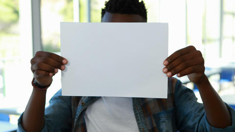 Schoolboy holding blank placard in classroom, Live Action
