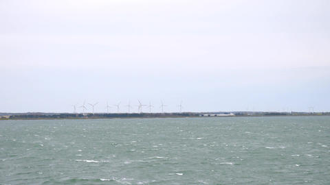 Ocean coast and farm of wind mill turbines along the shore beautiful landscape Footage