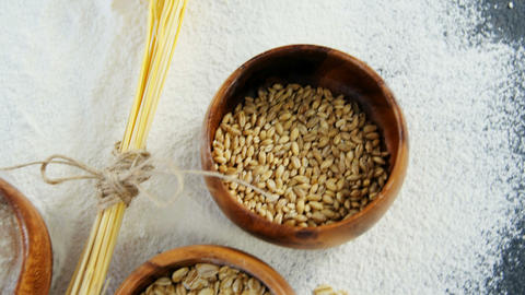 Wheat grains, sesame and flour in bowls Live Action